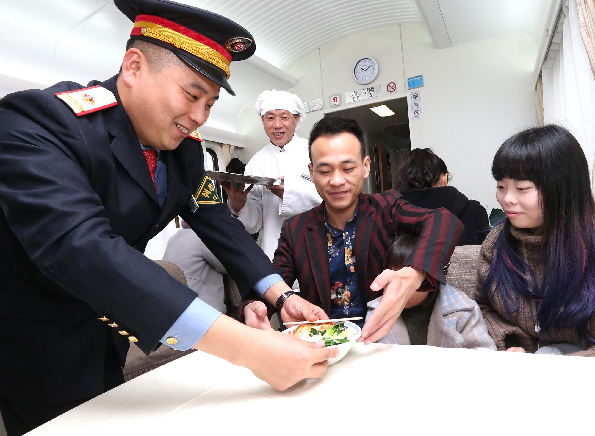 沪港列车车长张驰(左一)正在列车上为旅客送餐(1月17日摄)