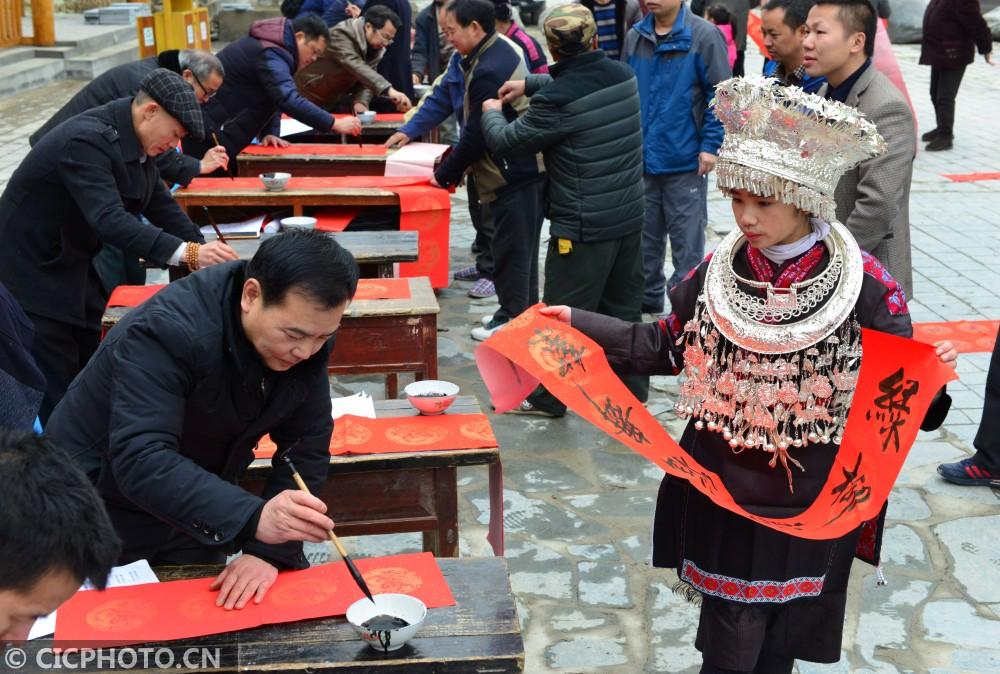 ↑1月16日,书法志愿者在贵州省剑河县观么镇巫包苗寨为村民写春联。CICPHOTO/杨文斌 摄