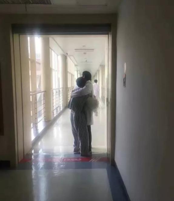 ↑ 1月16日,浙江大学医学院附属第二医院骨科医生胡何佳在病房走廊里,抱住突发躁狂病人。新华社发