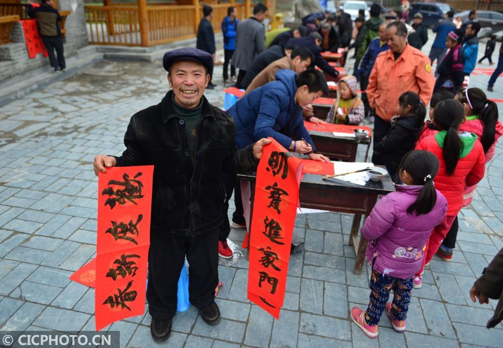 ↑1月16日,村民在贵州省剑河县观么镇巫包苗寨展示新领到的春联。CICPHOTO/杨文斌 摄