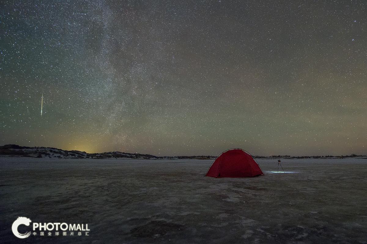 ↑1月4日,在内蒙古乌兰布统,一颗流星划过露营地的上空。CICPHOTO/高尚国 摄