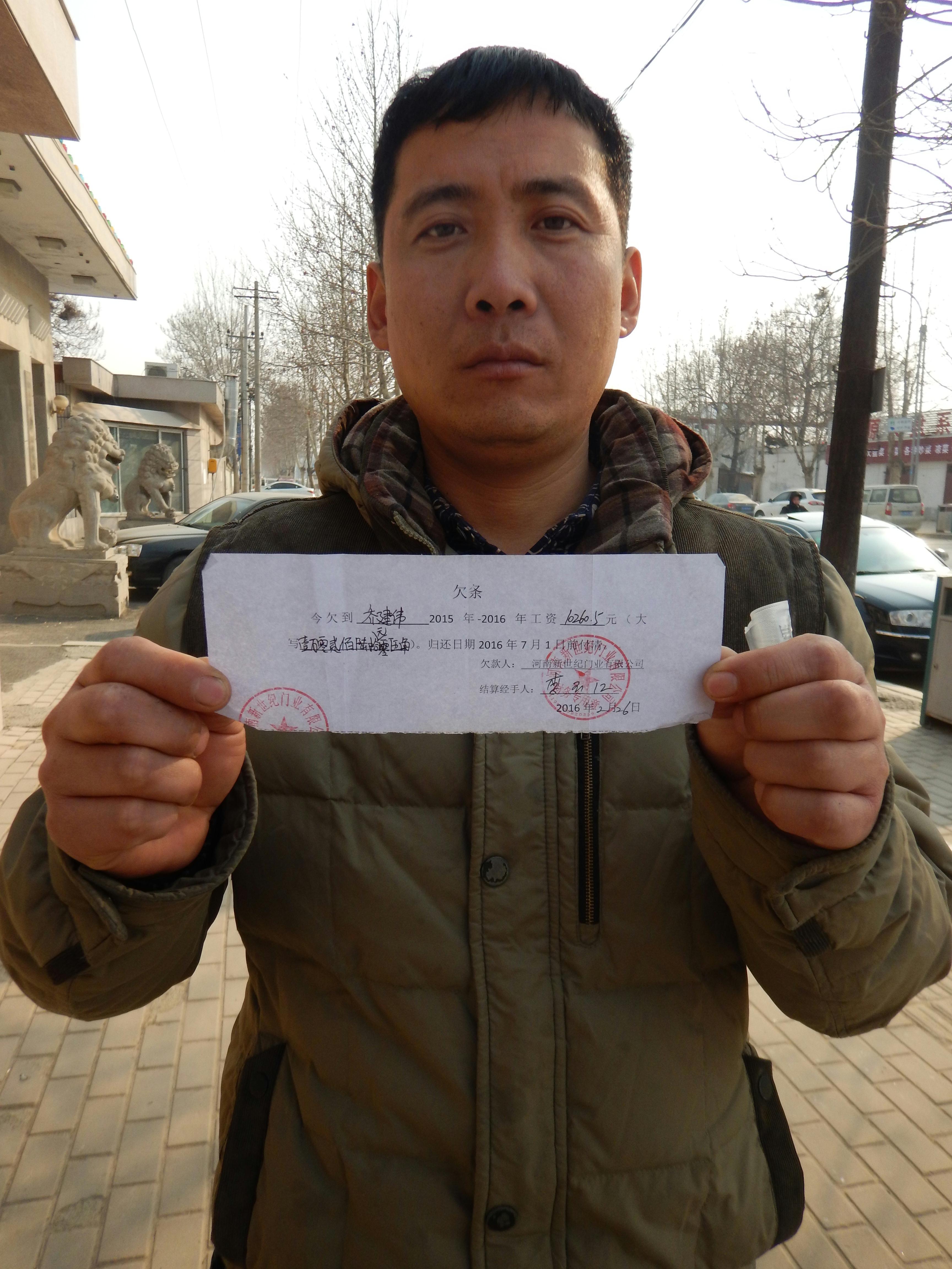 河南清丰县农民工乔建伟向记者展示河南新世纪门业有限公司开具的欠条。新华社记者 马意翀 摄