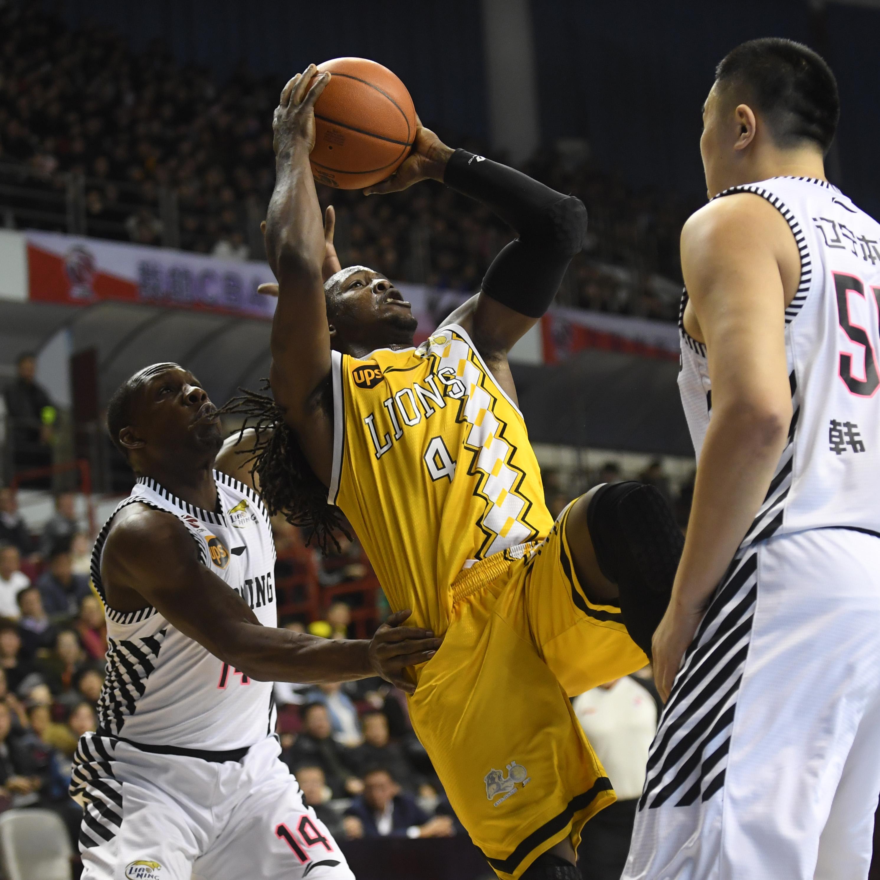 图为浙江广厦队球员福特森(中)在比赛中投篮。