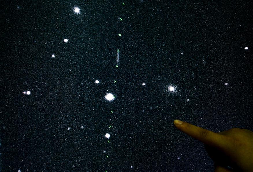 2016年9月7日,紫金山天文台盱眙观测站的观测员展示当晚近地天体望远镜拍摄到的近地小行星的运动状态——一条白色光带正沿着绿色十字叉所示的预报轨道运行。新华社照片