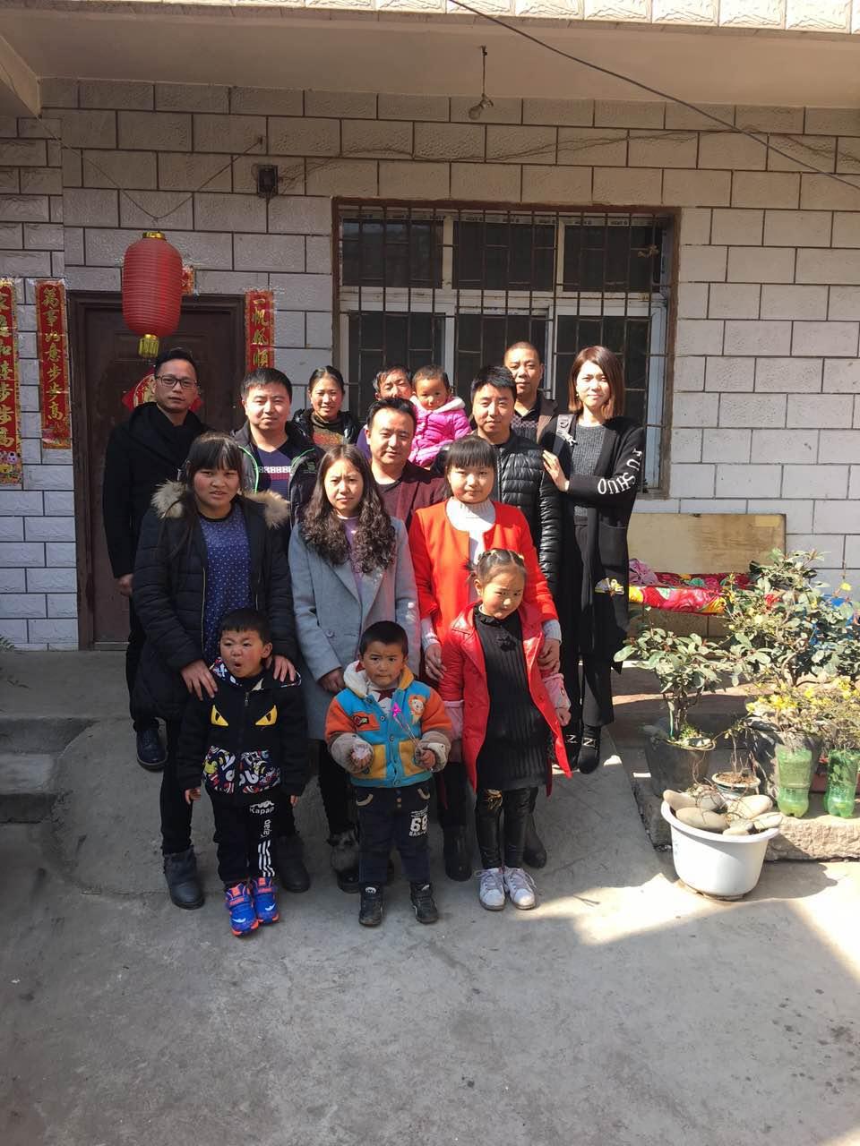 ↑ 1月30日,林志刚(后排左一)在云南昭通拜年时与员工家庭合影。新华社发