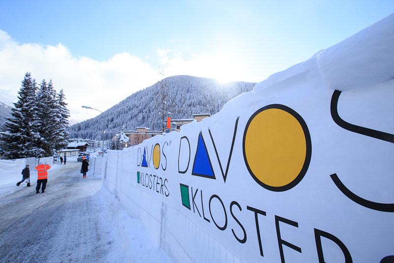1月16日,在瑞士冰雪小镇达沃斯,行人经过达沃斯宣传标志。新华社记者 徐金泉 摄