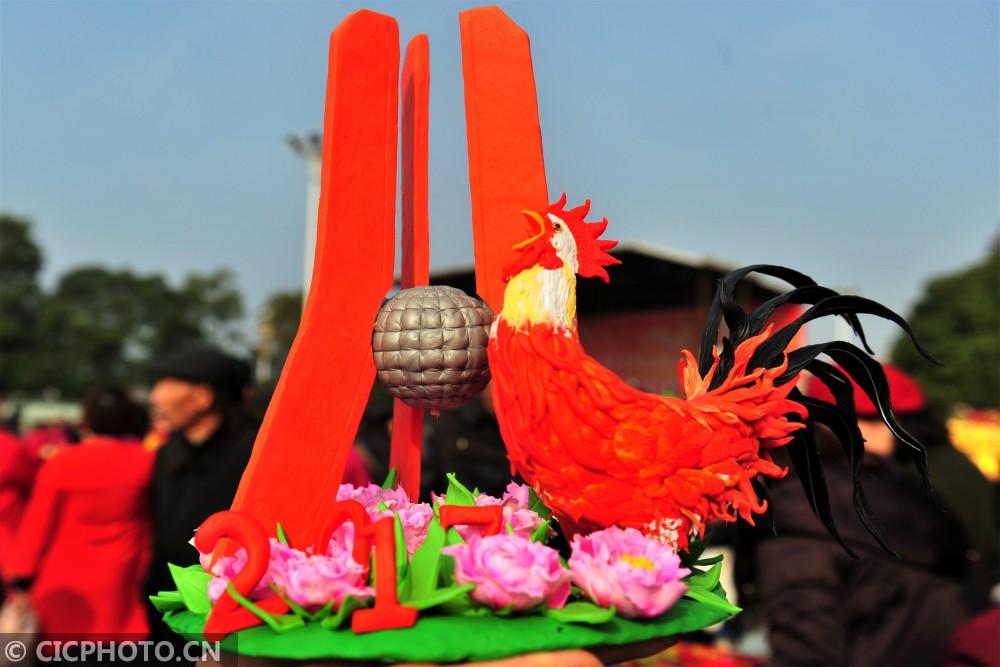 """↑2月10日,湖北省宜昌市夷陵区民间艺人艾民制作的面塑作品""""金鸡迎春""""。"""