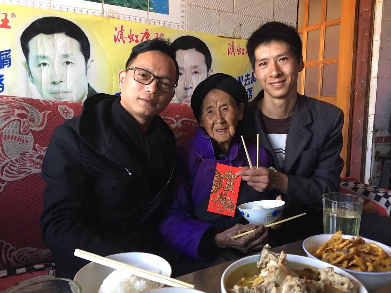 ↑ 1月31日,林志刚(左)在云南曲靖籍员工周向成家中拜年时,向周向成的奶奶赠送红包。新华社发