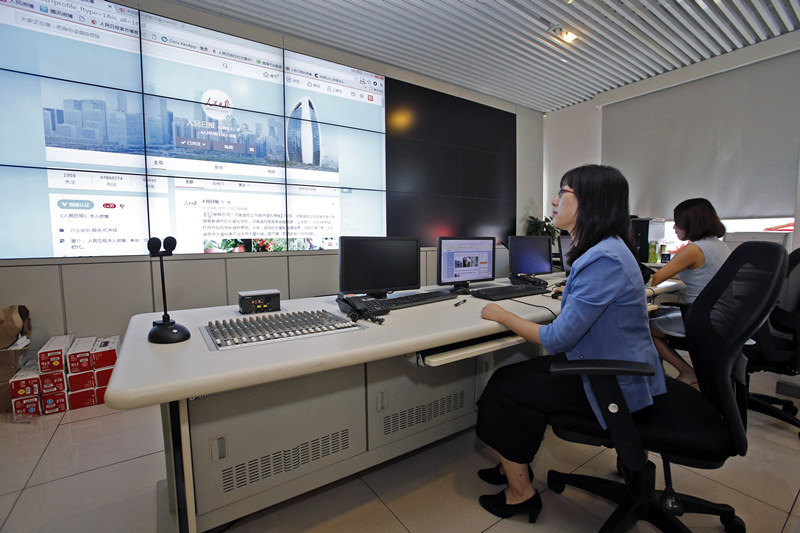 人民日报社新媒体中心微博运营室副主编苗苗(左)在微博运营室通过大屏幕查阅人民日报微博发布的内容(2016年8月31日摄)。 新华社记者 沈伯韩 摄