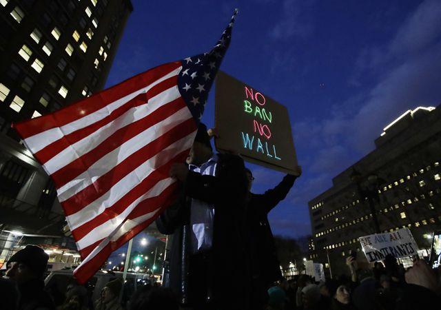 """2月2日,在美国纽约,一名抗议者手举美国国旗和""""不要禁令 不要高墙""""的标语,抗议总统特朗普的难民和移民新政。 新华社/美联"""