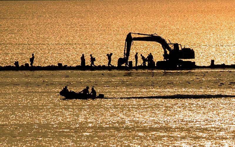 2016年7月13日,武警水电第七支队的战士在牛山湖坝上进行破垸前的准备施工作业。新华社记者 肖艺九 摄