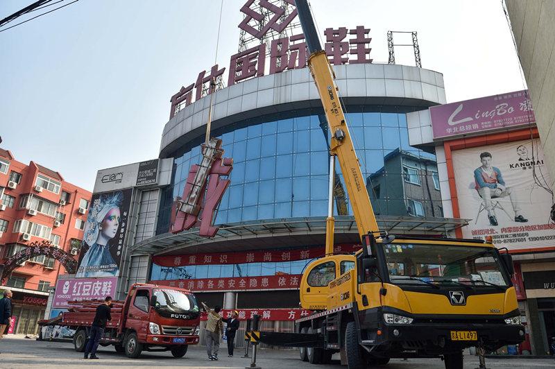 工人在拆除位于北京丰台大红门的方仕国际鞋城标志(2015年9月15日摄)。新华社记者 罗晓光 摄