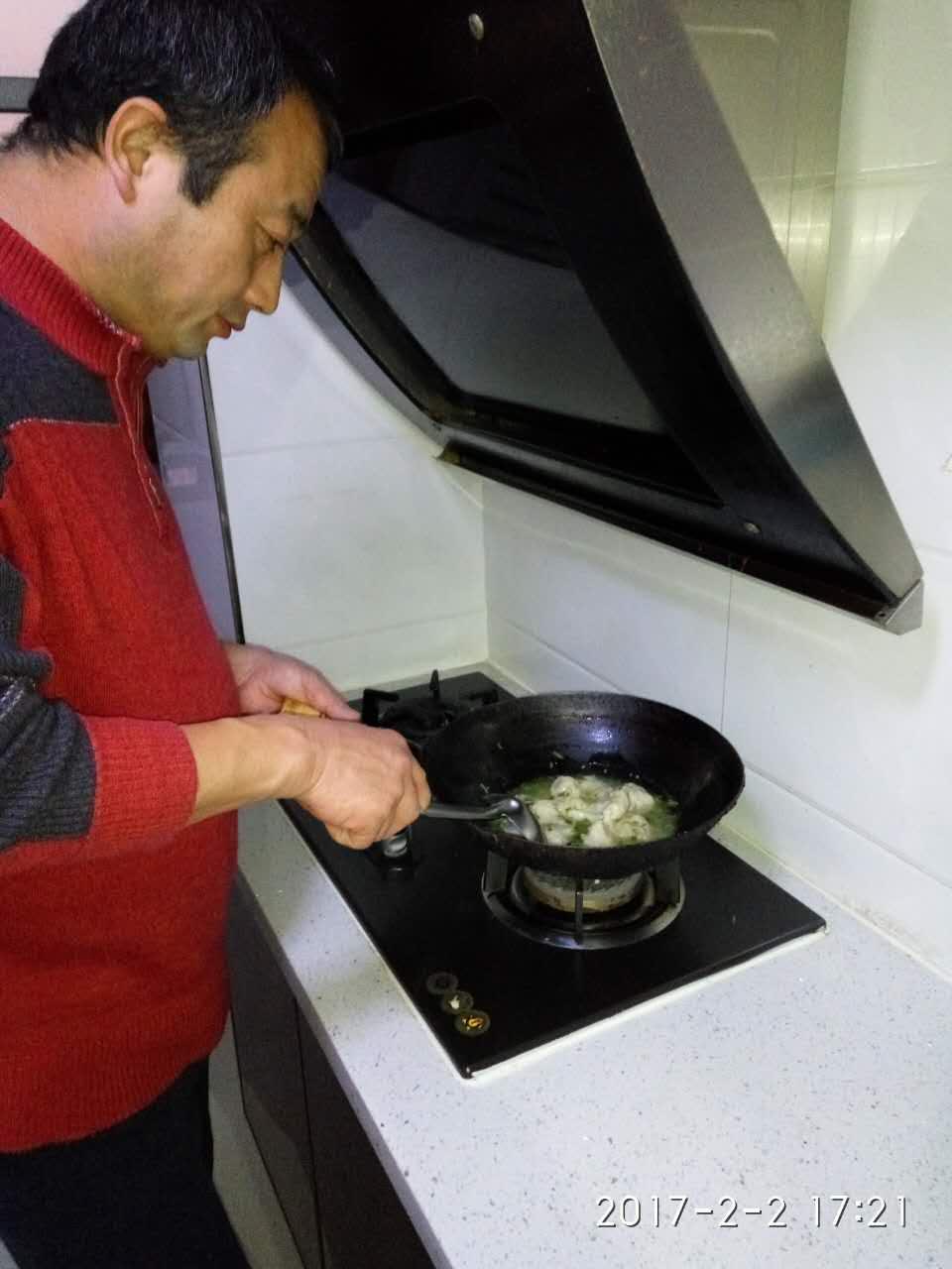 2月2日,张忠祥在家为出院在家的妻子准备晚餐。新华社发