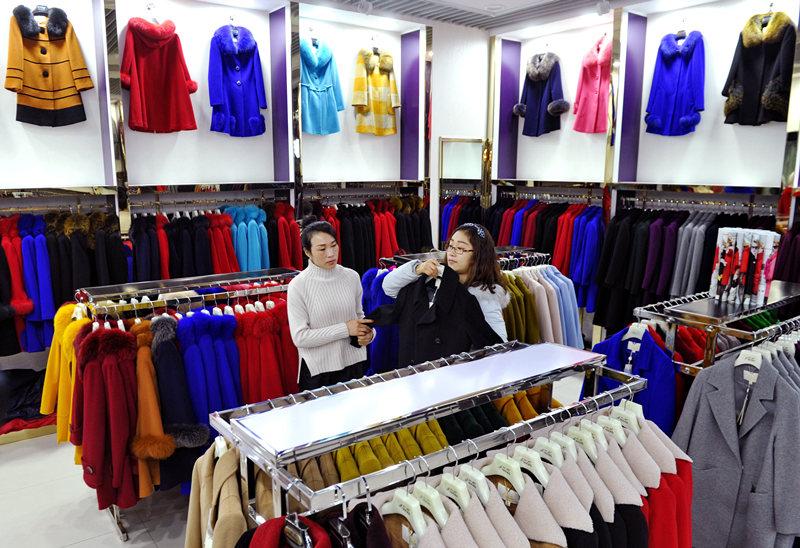 2月7日,从北京迁到沧州明珠商贸城的服装商户在帮助消费者挑选服装。新华社记者 牟宇 摄