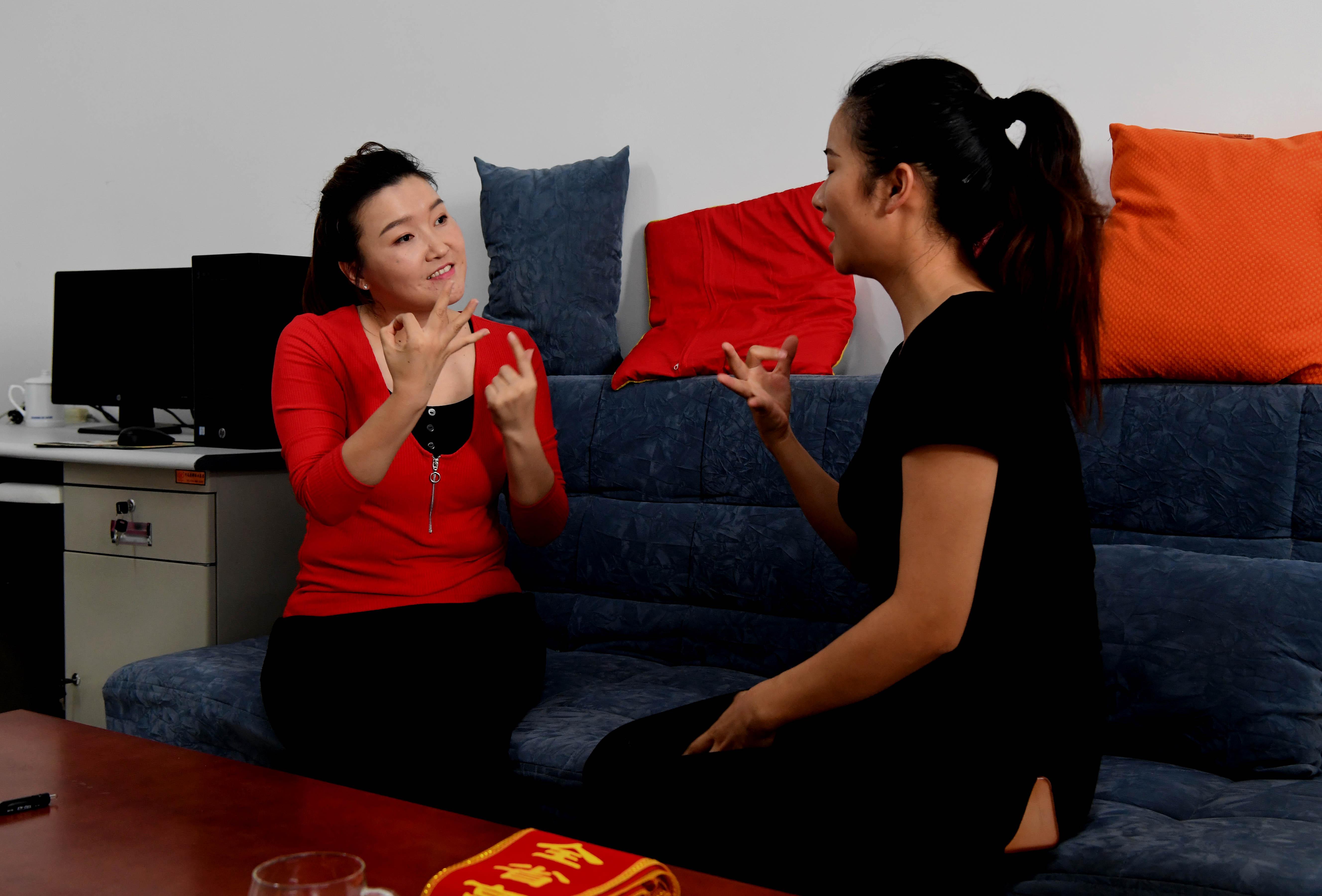 9月6日,董晶晶在办公室用手语跟学生聊天谈心.