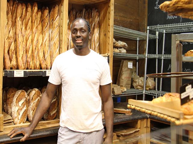 """16日,""""巴黎榖仓""""面包店,博迪安与他的招牌法棍。(新华社记者张曼摄)"""