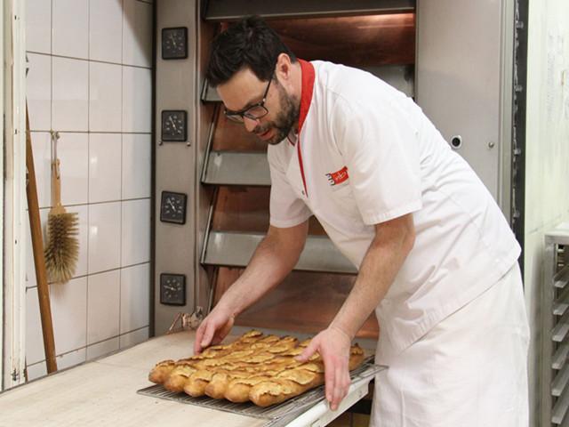"""16日,""""巴黎榖仓""""面包店,史蒂文从烤炉中取出制作好的法棍面包。(新华社记者张曼摄)"""