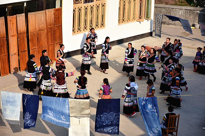 蔡群公司里的绣娘们在房前的空地上边晒蜡染边载歌载舞。新华社记者向定杰2月21日摄