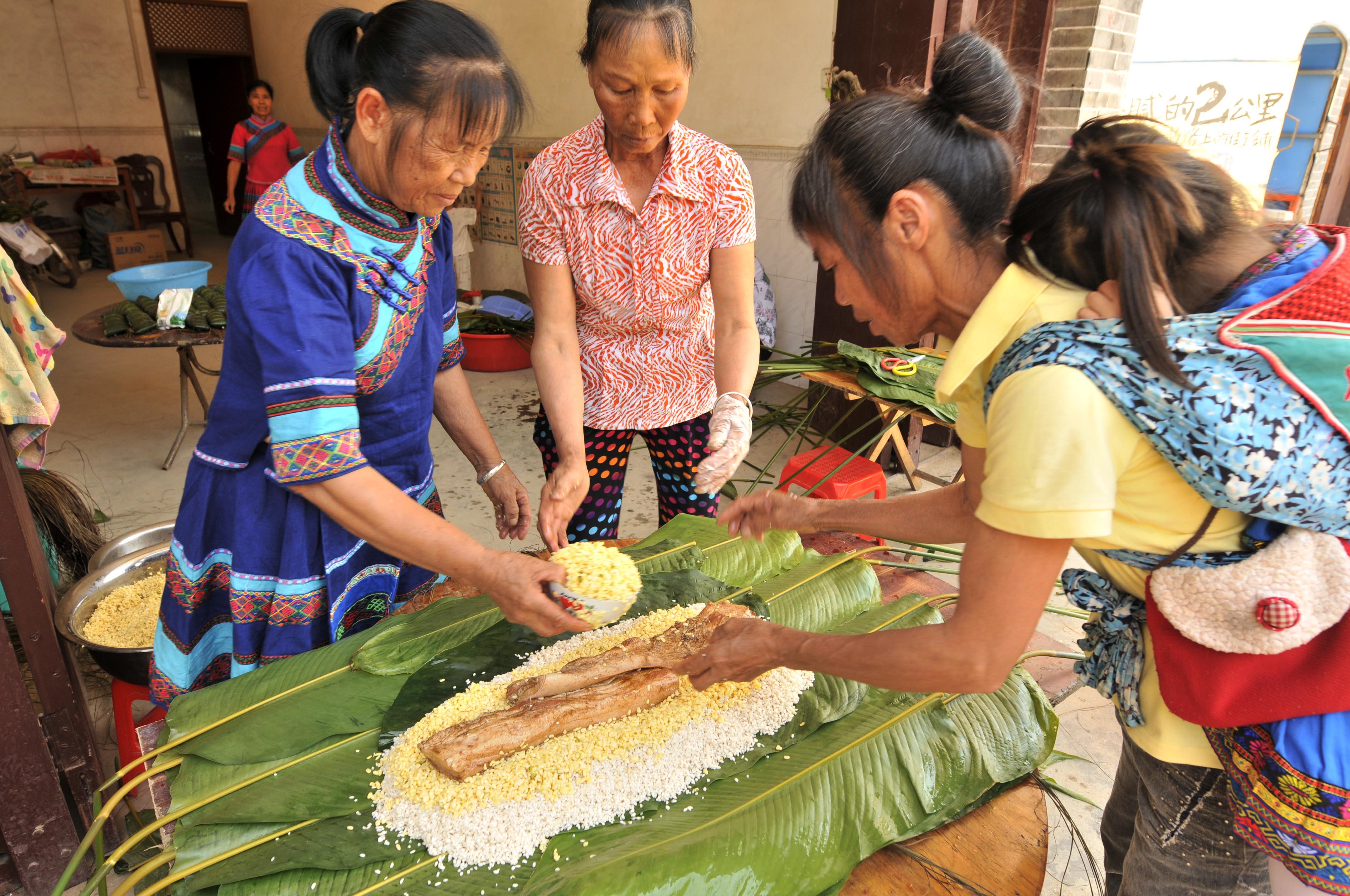 图为广西几名壮族妇女在包重达10斤的枕头粽。新华社发(潘华清 摄)
