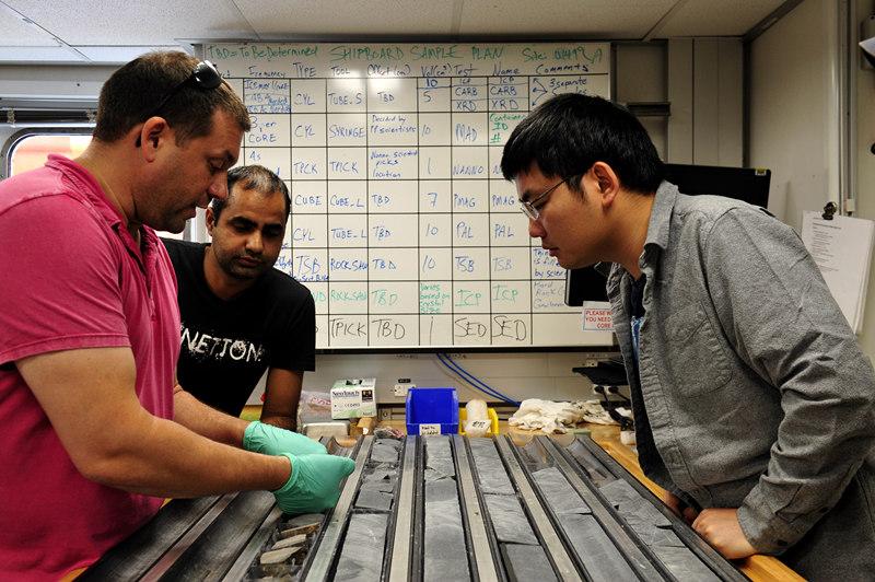 """在第三次南海大洋钻探中,中外科学家在美国""""决心""""号大洋钻探船上观察研究玄武岩岩芯样品。新华社记者张建松 摄"""