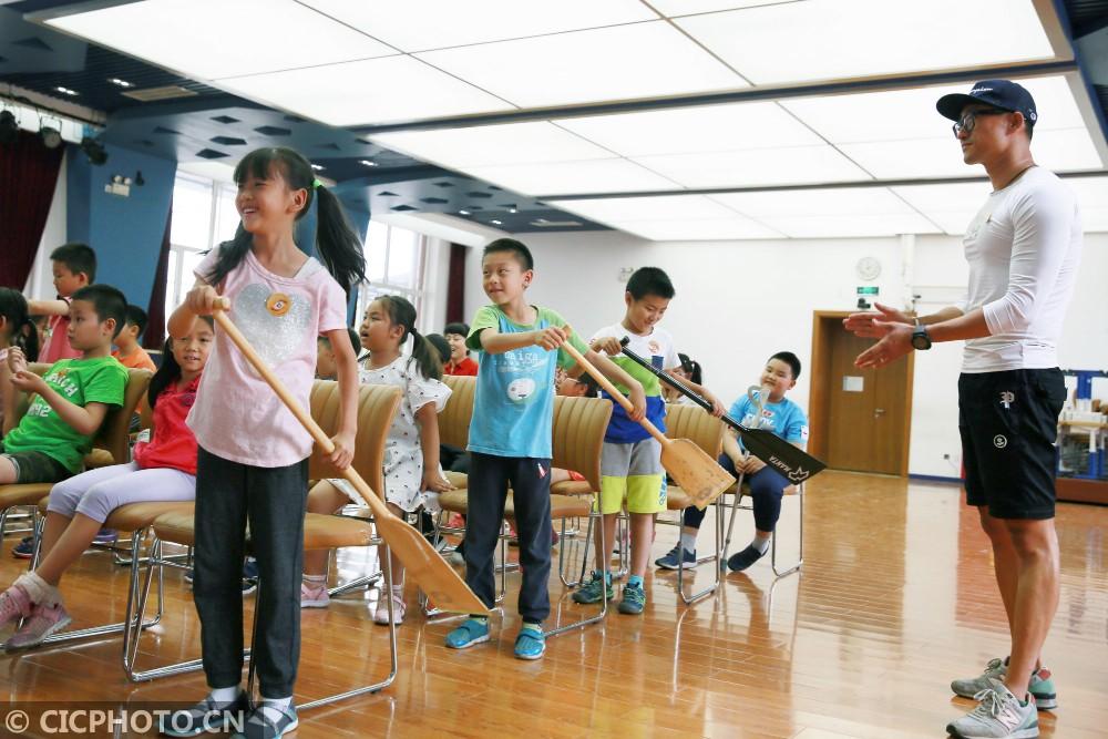 ↑6月5日,北京史家小学的学生在北京TBT龙舟队队员的指导下学习使用龙舟桨。