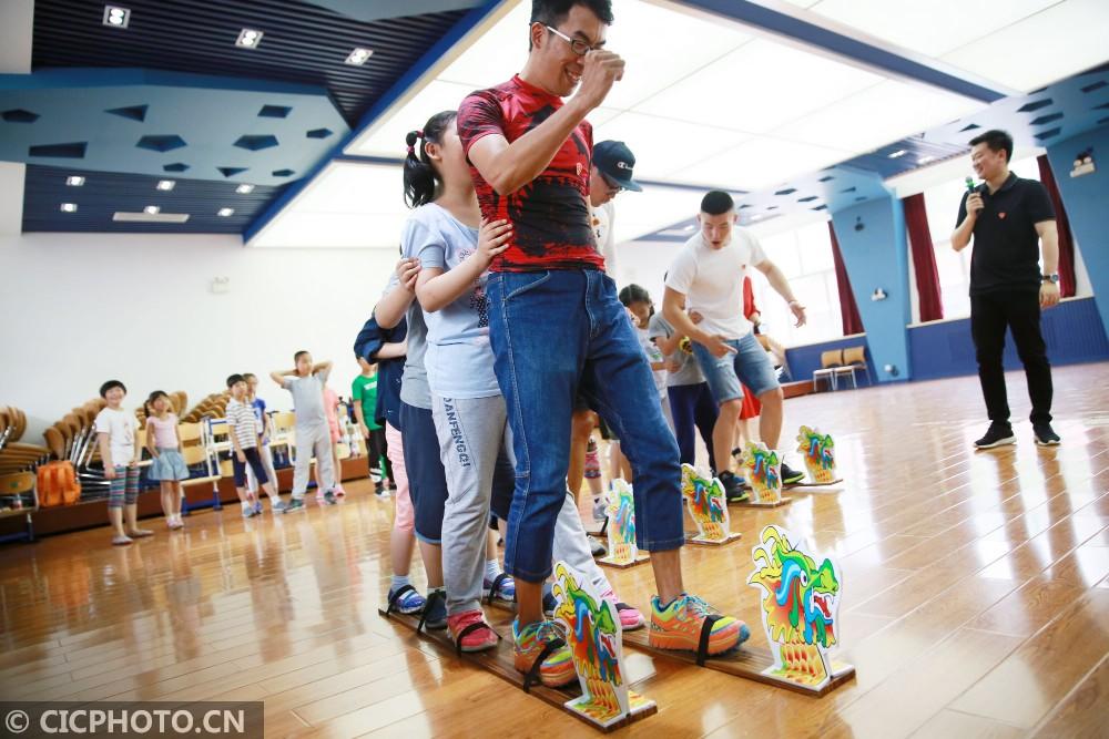 ↑6月5日,北京史家小学的学生们与北京TBT龙舟队队员一起进行旱龙舟比赛。