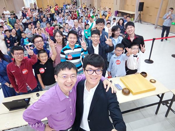 ↑柯洁(前右)、爱棋道CEO王煜辉(前左)和小棋手们玩自拍。