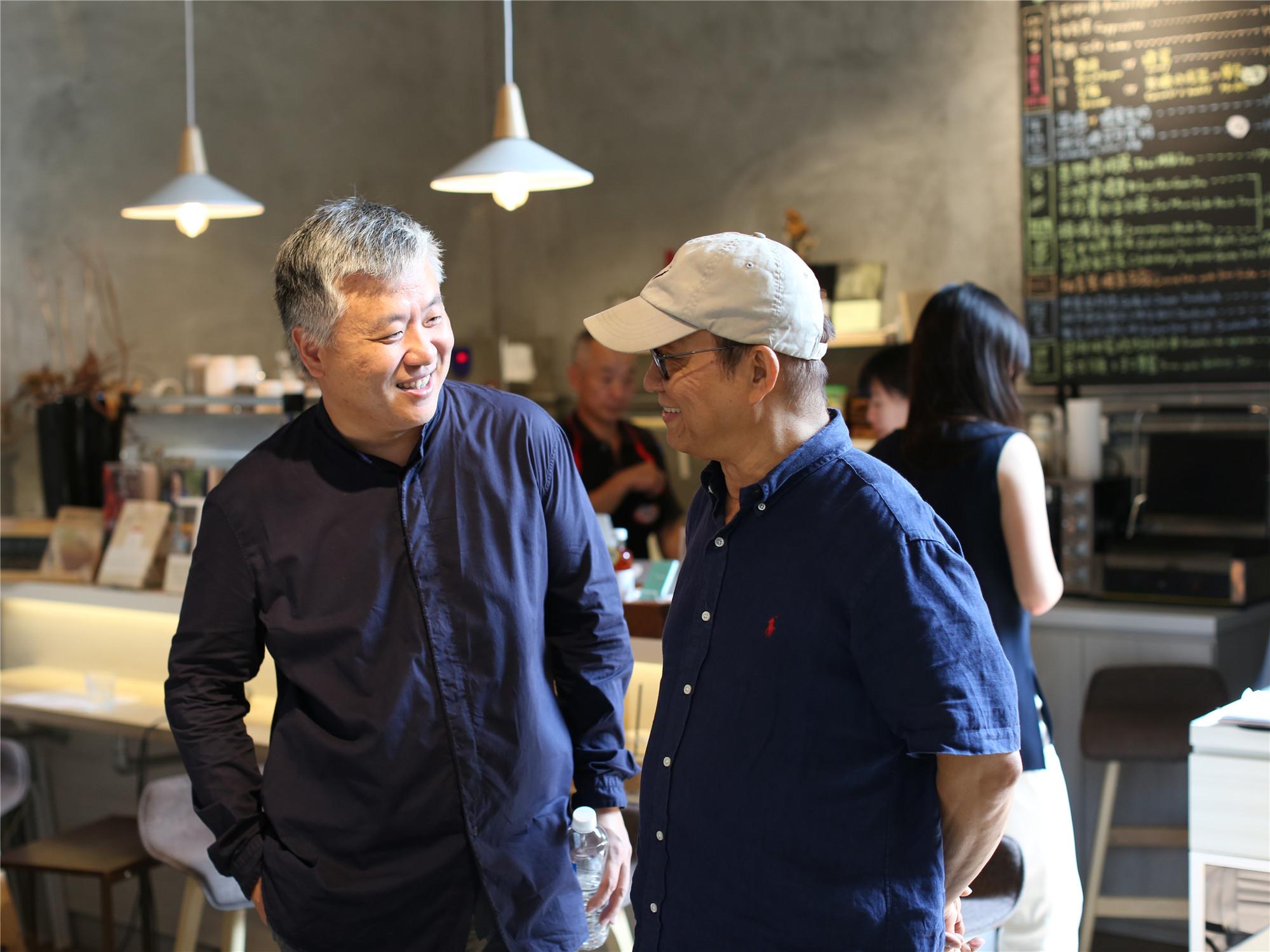 图为电影《我在故宫修文物》导演萧寒(左一)与剪辑师廖庆松在台北举行的记者会上相谈甚欢。新华社记者 陈君 摄
