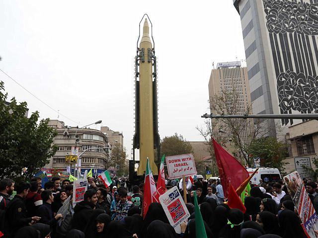 伊朗民众围聚在展出的导弹周围。(新华/法新)