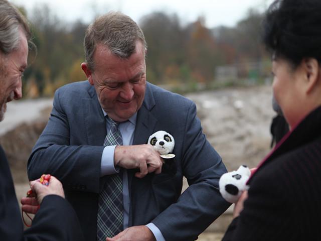 11月16日,哥本哈根,拉斯穆森(中)出席熊猫馆奠基仪式,将一只熊猫纪念品放进胸前口袋。(新华社记者石寿河摄;)