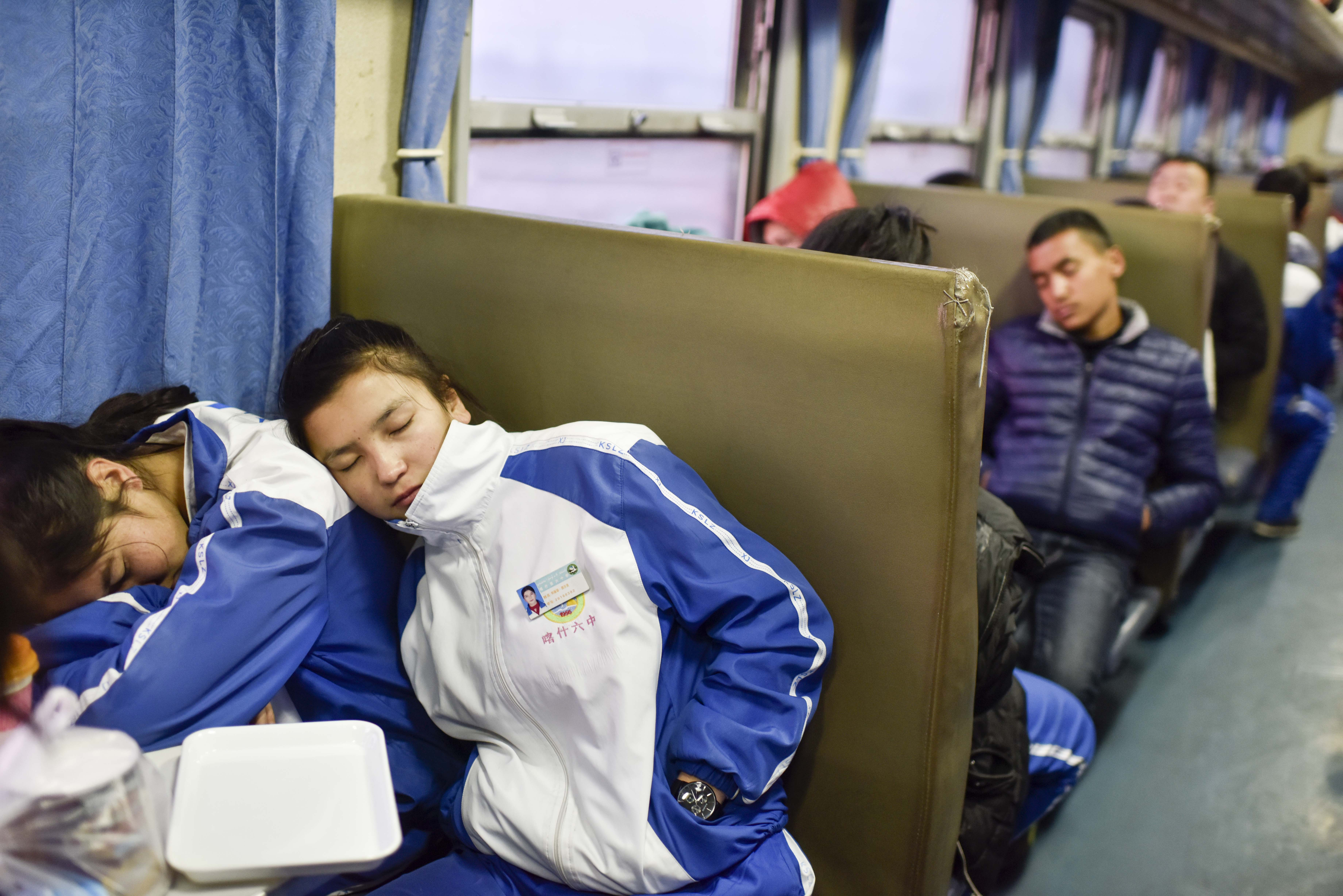 在由喀什开往和田饿5809次列车上,来自喀什六中的学生正在休息(11月24日摄)。每个月这些同学们回放一个小段假,他们会优先选择坐火车回家。因为坐火车安全票价也很低廉。