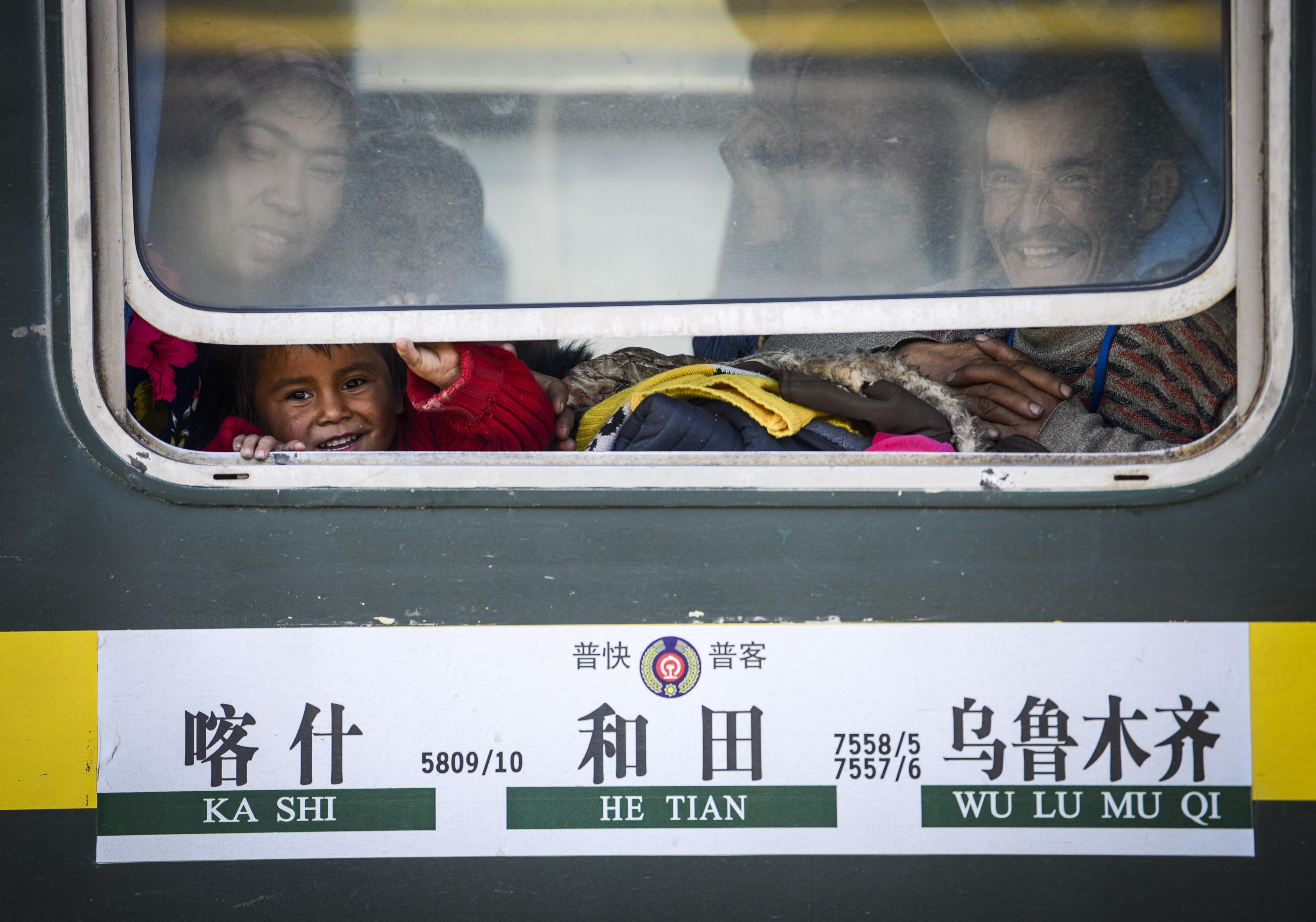 乘坐喀什开往和田的7557次列车的乘客坐在车厢里(11月24日摄)。