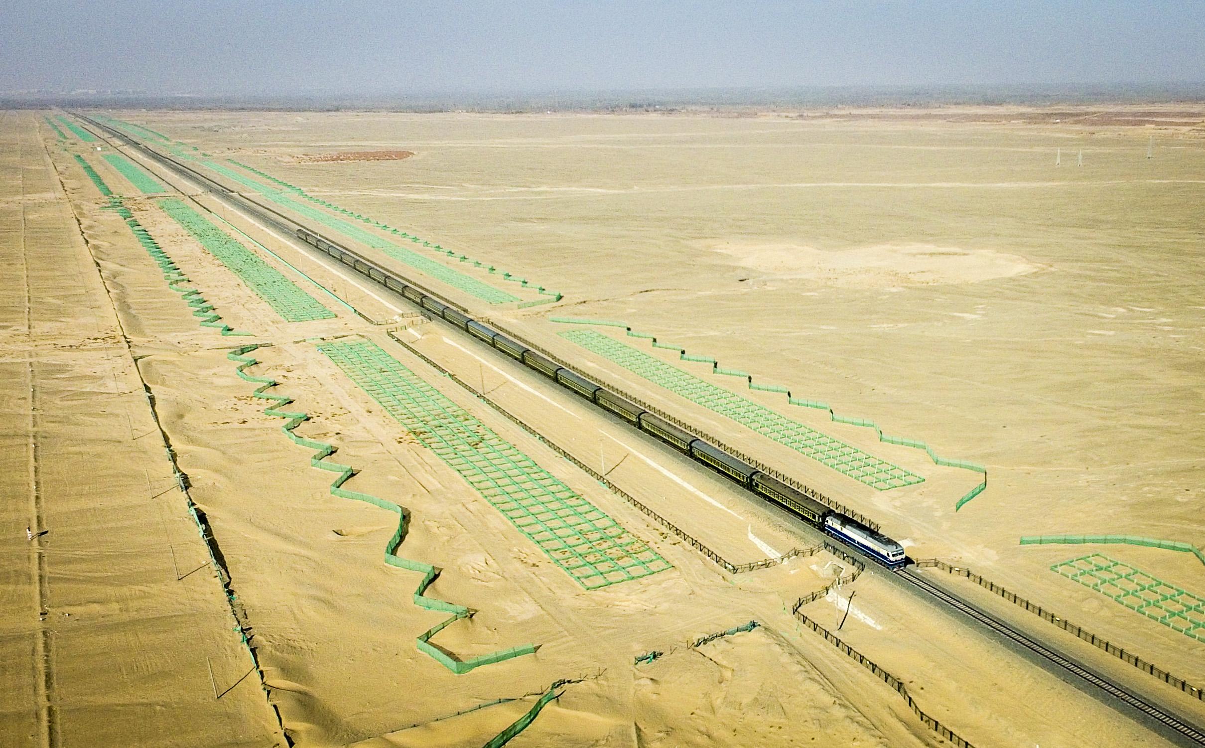 喀什-和田对开的绿皮火车行驶在喀什地区叶城县和和田地区皮山县之间的风沙区(11月26日摄)。为了防止流沙,铁轨两侧已经设置了绿色的防砂帐。