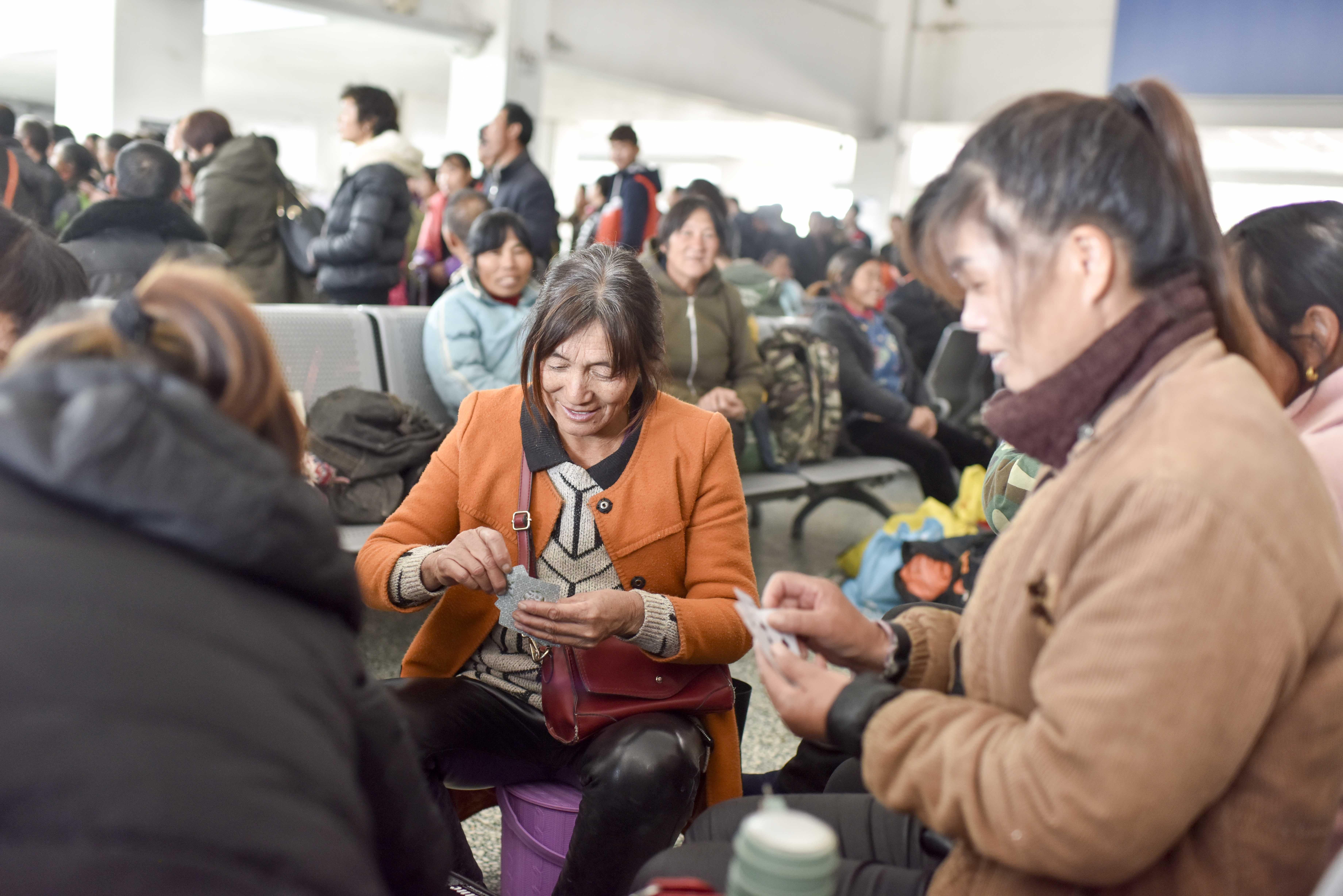 """在喀什火车站,准备乘车绿皮""""小慢车""""的乘客正通过打牌来消磨时光(11月23日摄)。"""