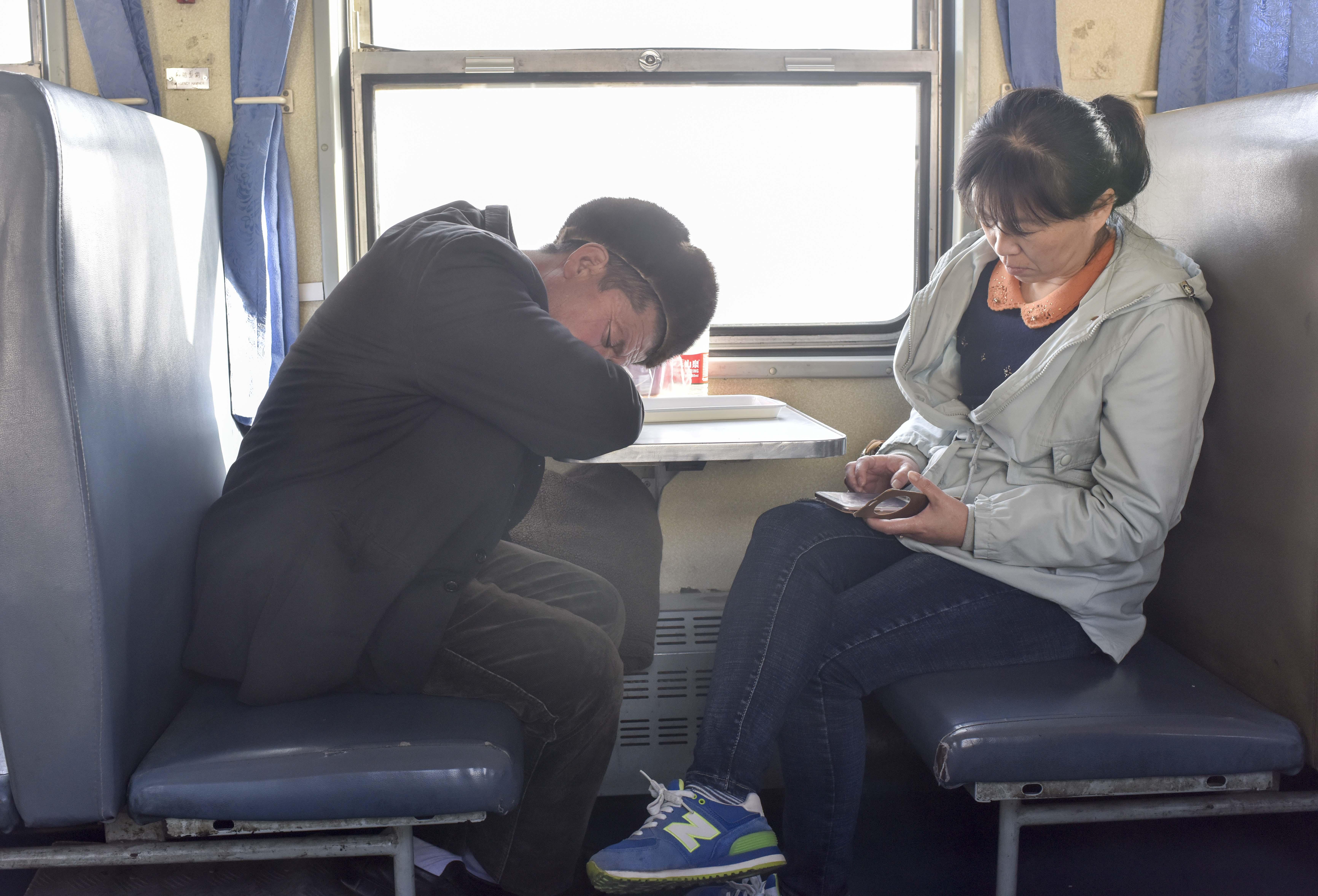 在由喀什开往和田饿5809次列车上,一位乘客正在看手机,另一位乘客正在休息(11月24日摄)。