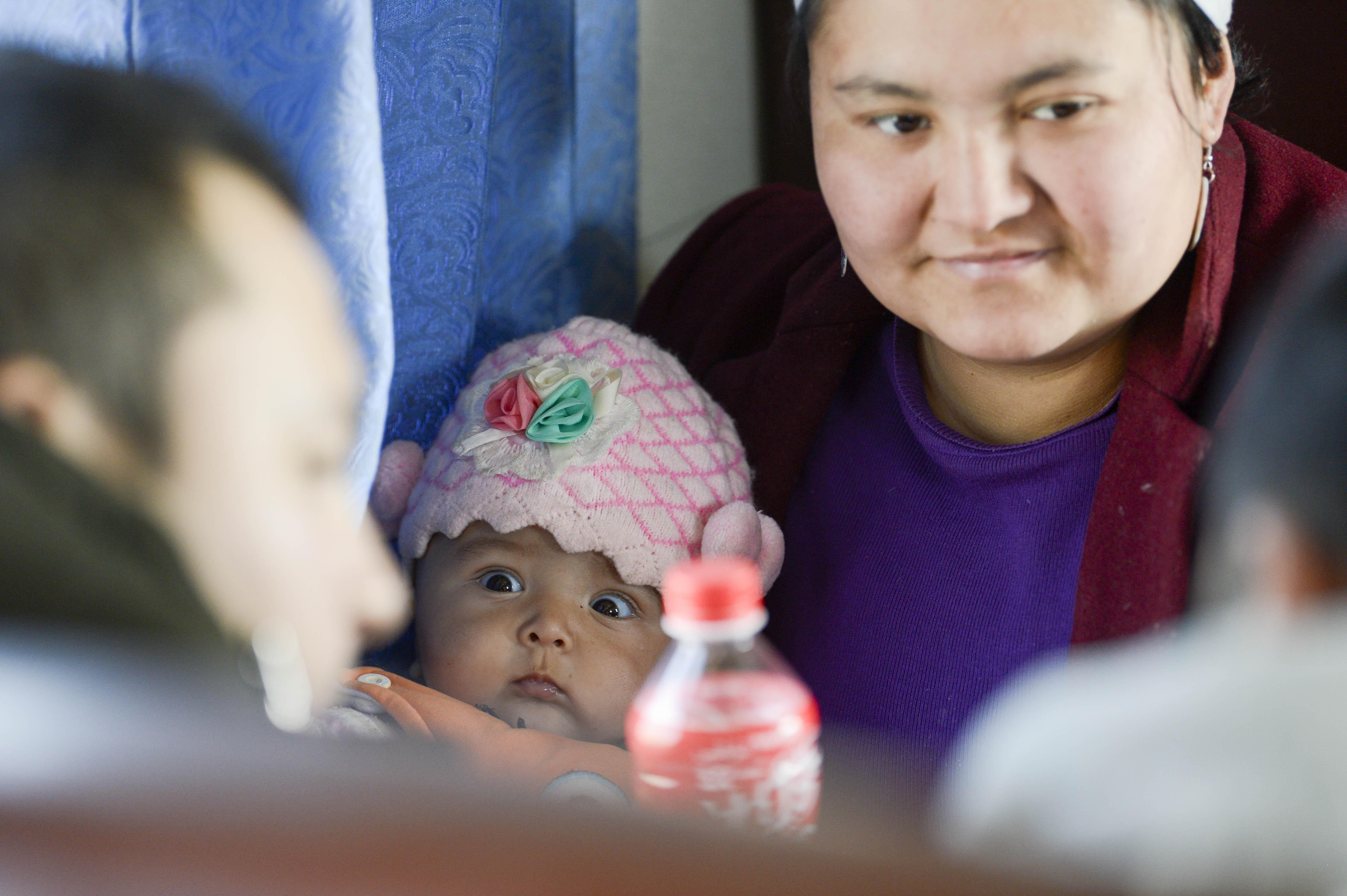 在5809次列车上,一位小乘客瞪大眼睛观察着周围陌生的环境(11月24日摄)。运行缓慢价格低廉的绿皮车正改变着过往的每一位旅客。