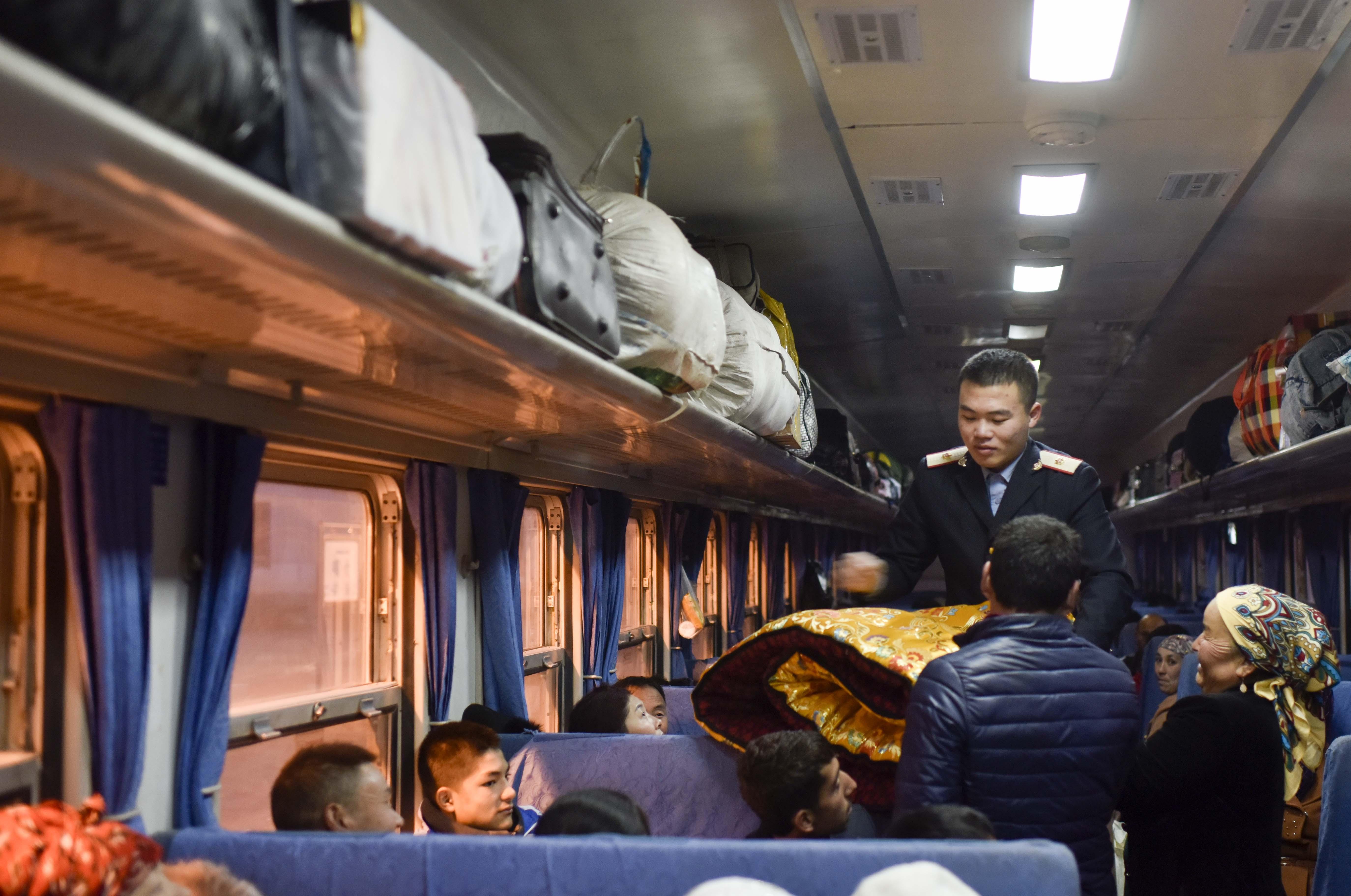 在由喀什开往和田饿5809次列车上,乘务员正在为旅客摆放行李(11月24日摄)。