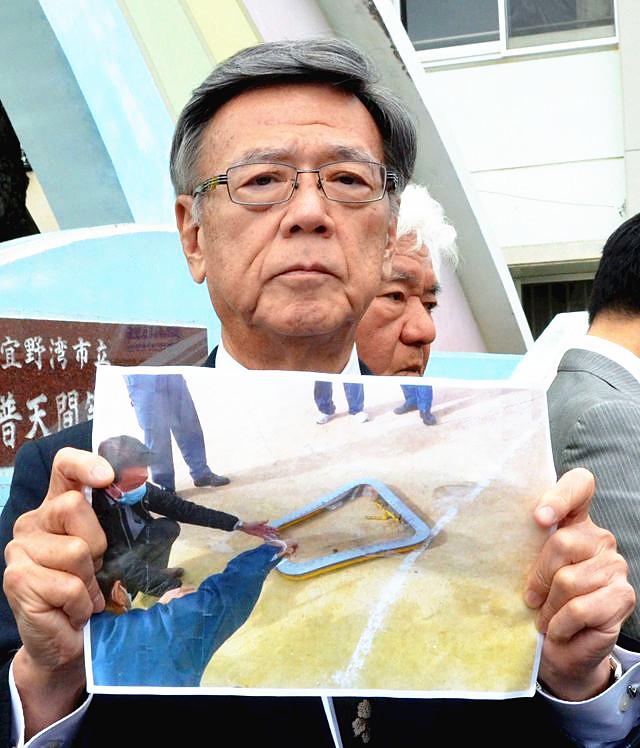12月13日,宜野湾,冲绳县知事翁长雄志向媒体记者展示美军机坠物照片。(新华/美联)