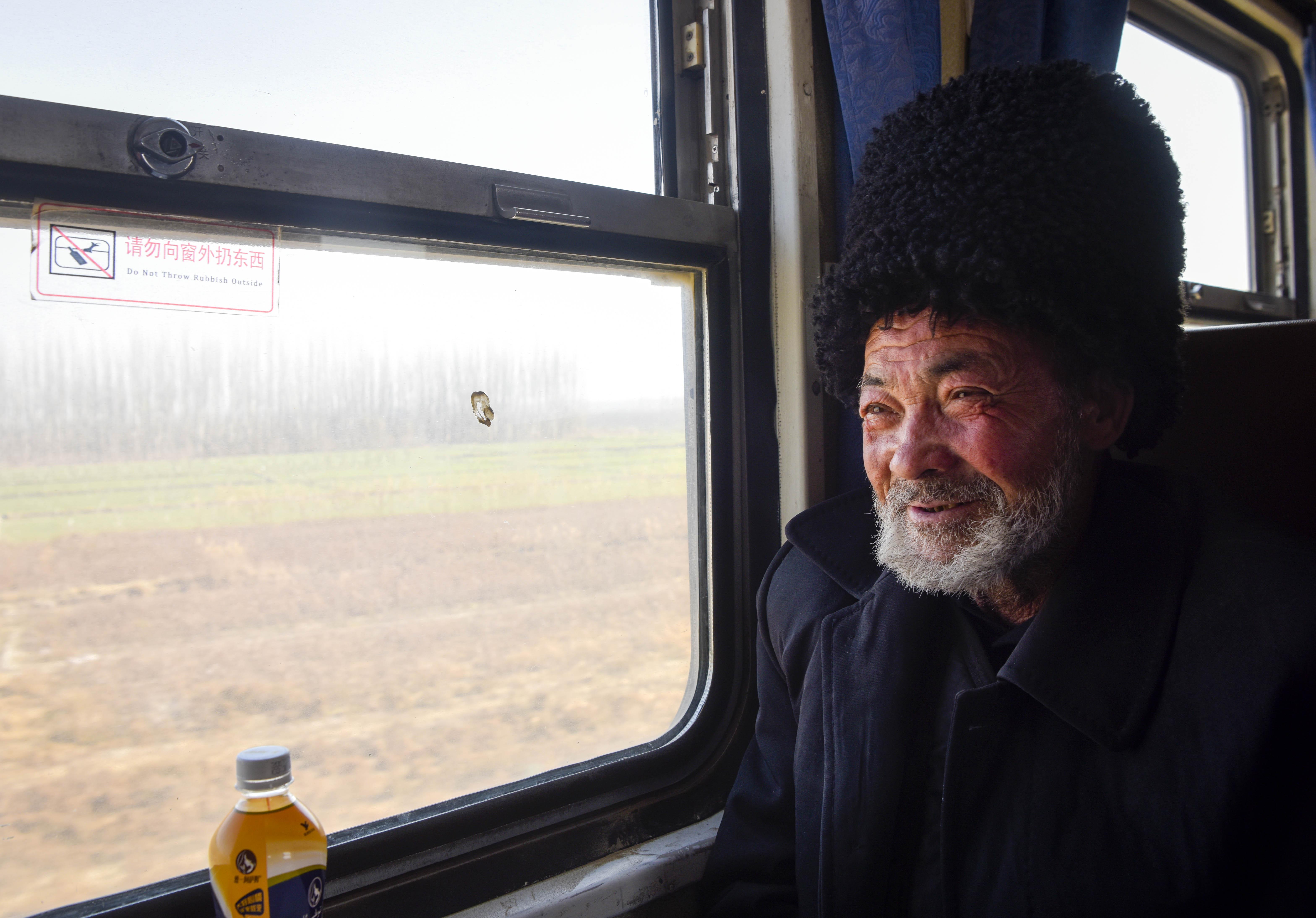 家住和田地区皮山县的买买提·阿皮孜坐在由和田开往喀什的5810次列车上(11月25日摄)。今年77岁的他是第一次坐火车,他准备去喀什地区泽普县探亲。