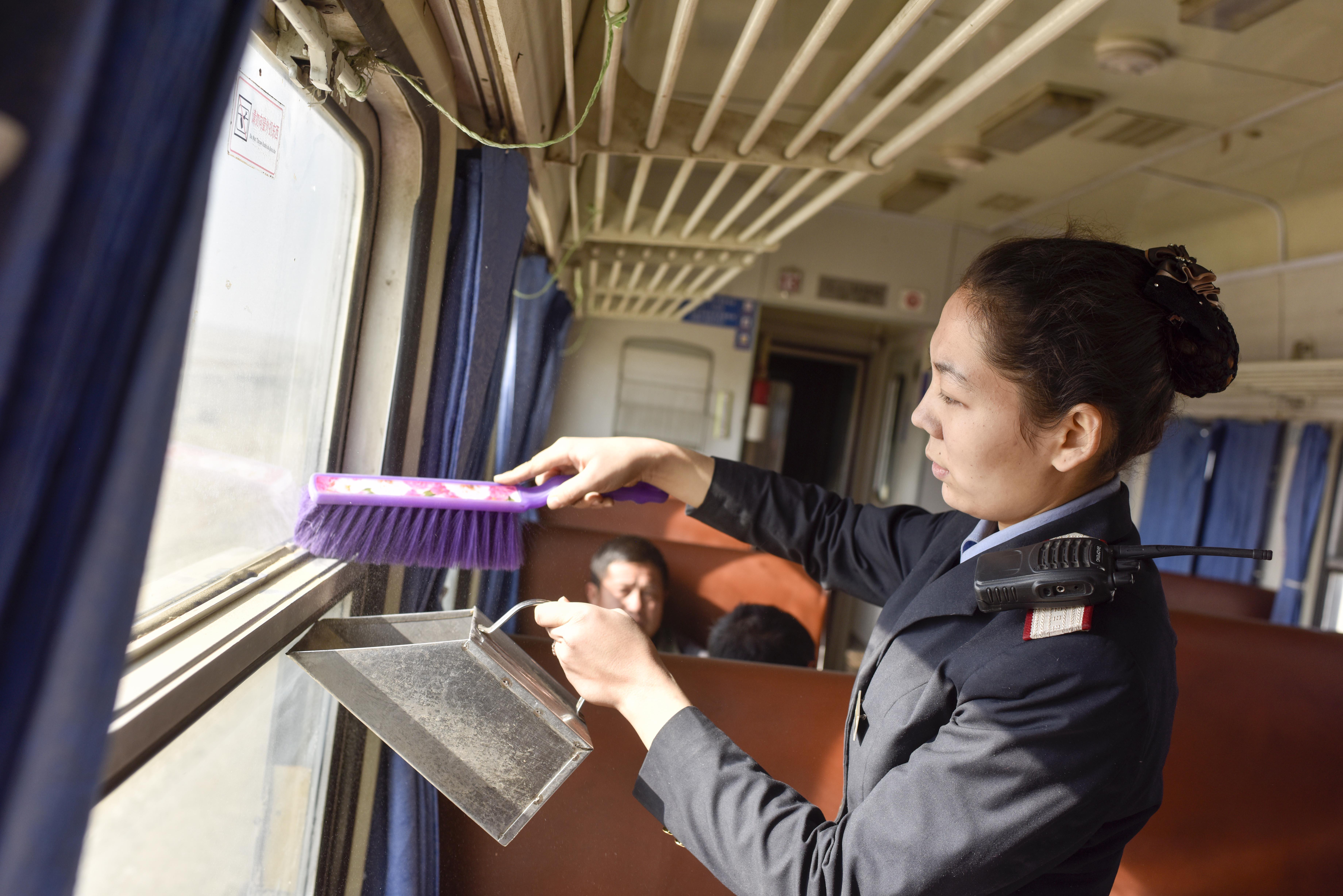 5809次列车正通过叶城县至皮山县的风沙区时,苏比努尔·塔叶尓正在打扫车厢里的傻子(11月24日摄)。
