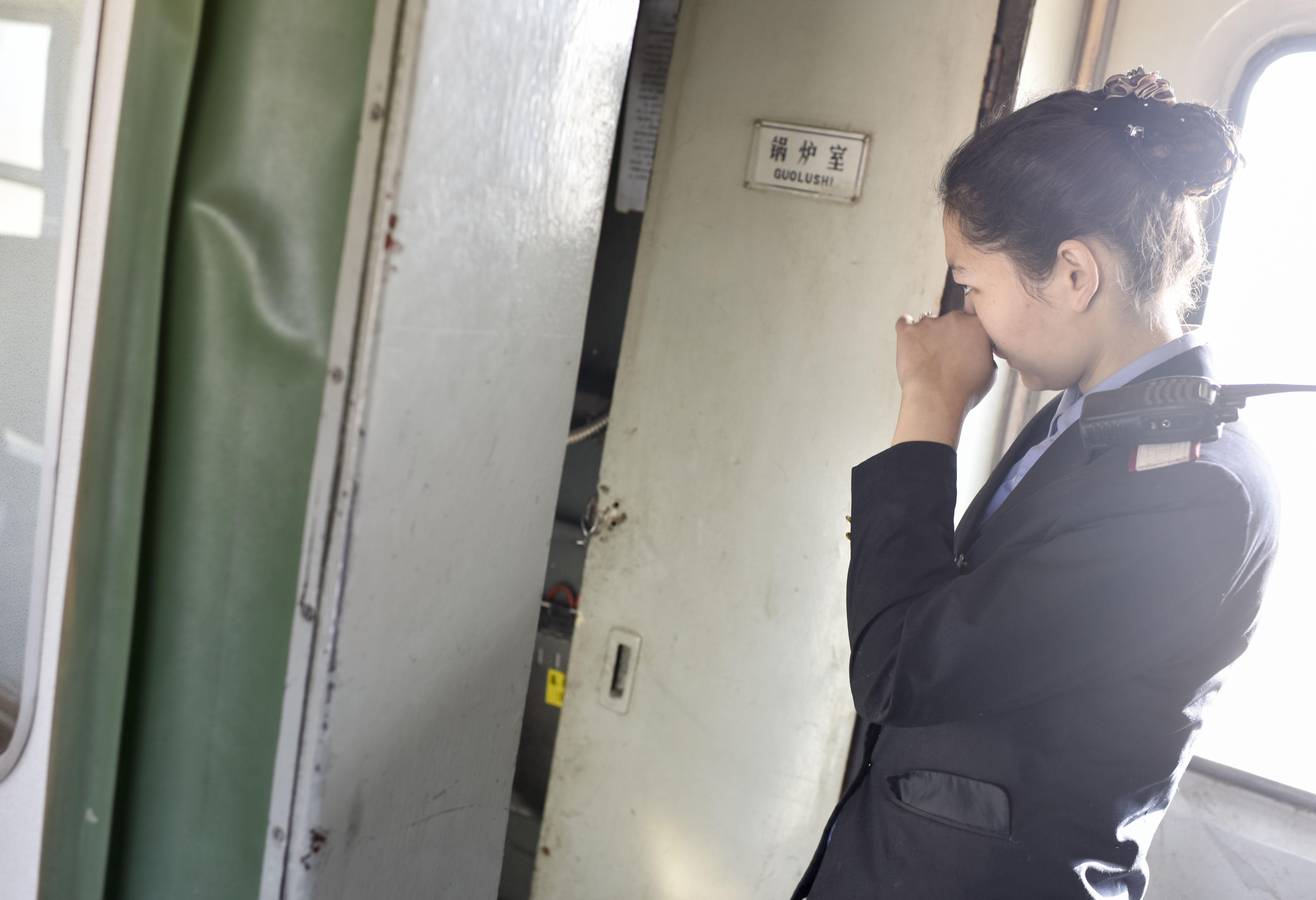在5809次列车上,列车员苏比努尔·塔叶尓正在给车厢加煤(11月24日摄)。由于绿皮车还是使用比较老旧的25B型车体,列车供暖只能通过烧煤来实现。这对列车员提出了更高的要求。