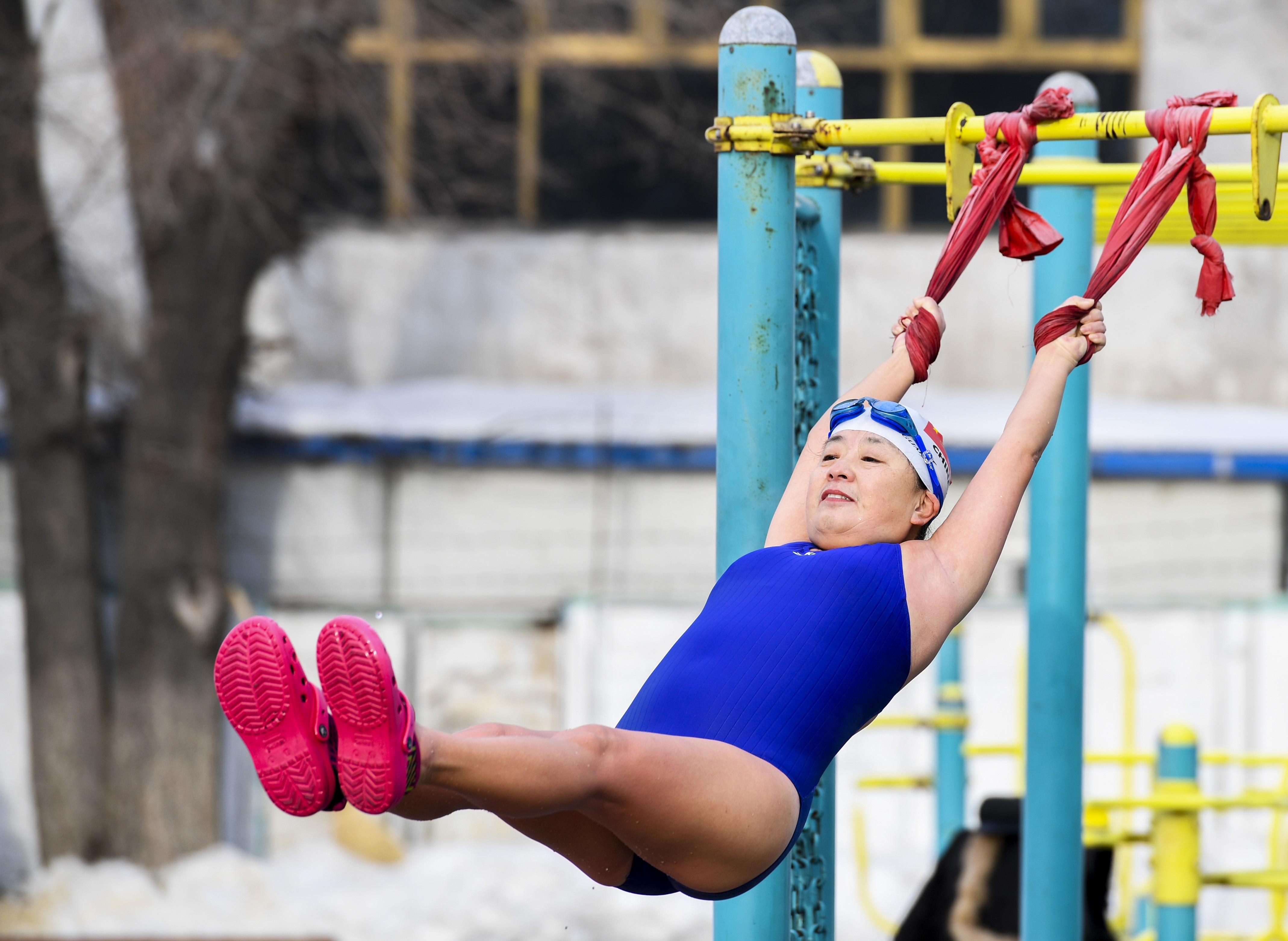 1月12日,一名冬泳爱好者在乌鲁木齐市红山冬泳俱乐部做热身运动。 新华社记者胡虎虎摄