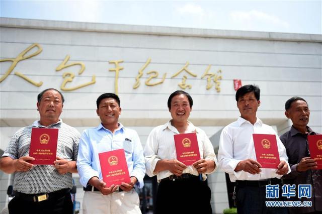 小岗村农民展示领到的《农村土地承包经营权证》(2015年7月8日摄)。新华社记者刘军喜摄