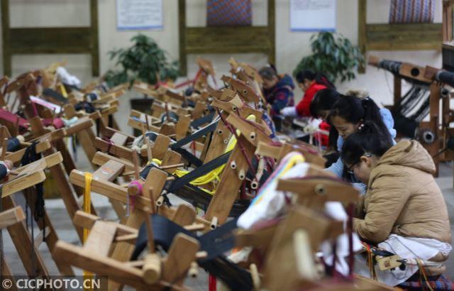 ↑12月24日,在湖南省张家界市武陵源区乖幺妹土家织锦基地,工人在制作土家族织锦产品。CICPHOTO/吴勇兵 摄